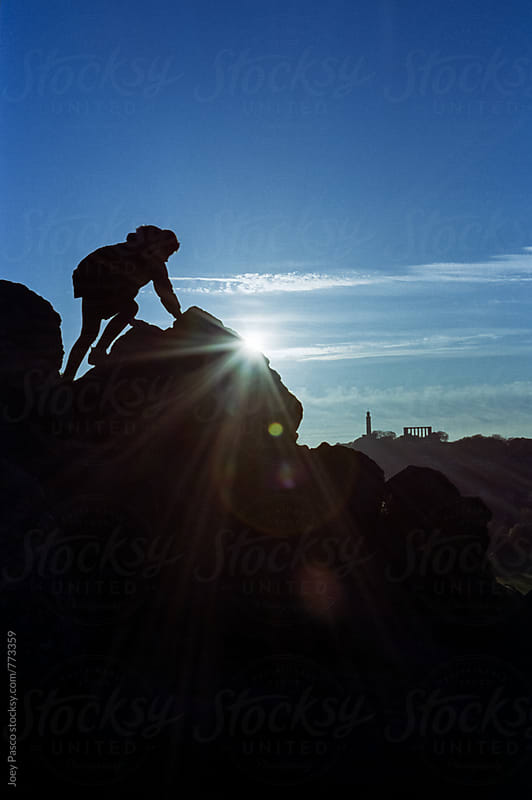 Silhouette on Arthur's Seat with Calton Hill in background by Joey Pasco for Stocksy United