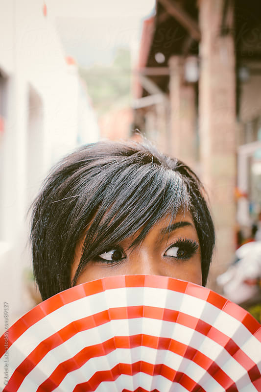 Black girl smiling behind red and white fan by Gabrielle Lutze for Stocksy United