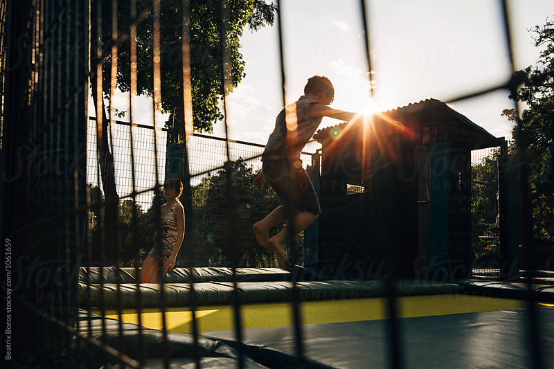 Boy jumping on a trampoline behind the bars at Sunset by Beatrix Boros for Stocksy United