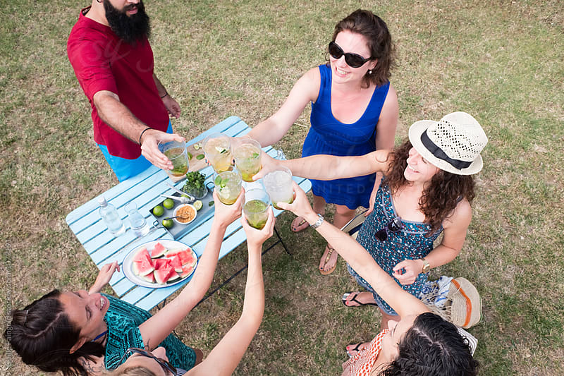 Friends toasting with homemade mojito in garden by Guille Faingold for Stocksy United