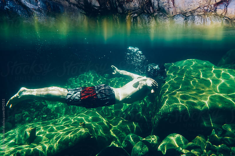 split perspective of a man swimming in a clear mountain stream rockpool by Micky Wiswedel for Stocksy United