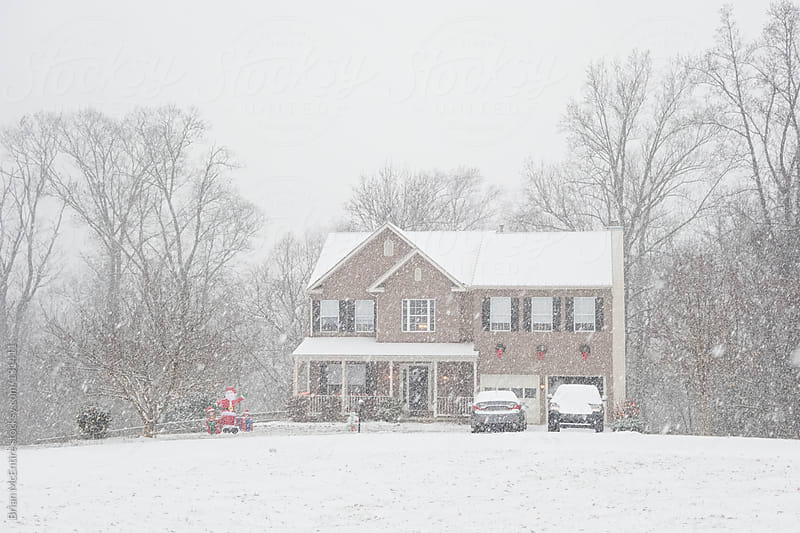 Heavy Snow Falling by American Brick Home Decorated for Christmas by Brian McEntire for Stocksy United