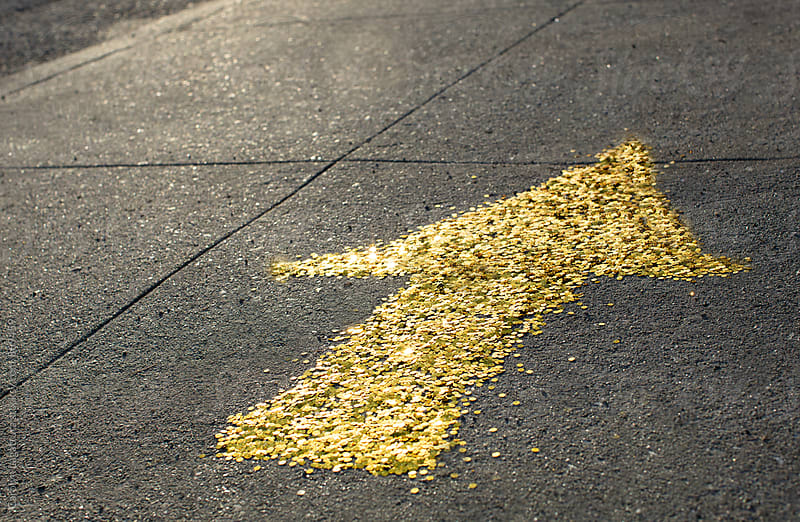 Gold sequin arrow pointing forward on the sidewalk by Carolyn Lagattuta for Stocksy United