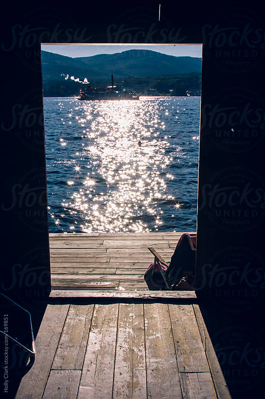 Looking out of a dockhouse at a swimmer watching a steamboat cruise by on a lake. by Holly Clark for Stocksy United