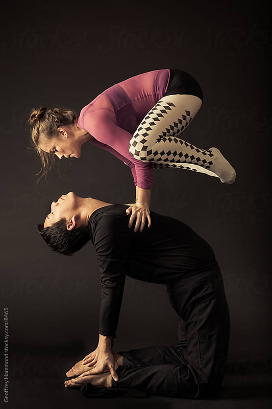 Acroyoga Pair: Crow on Camel Pose by Geoffrey Hammond for Stocksy United