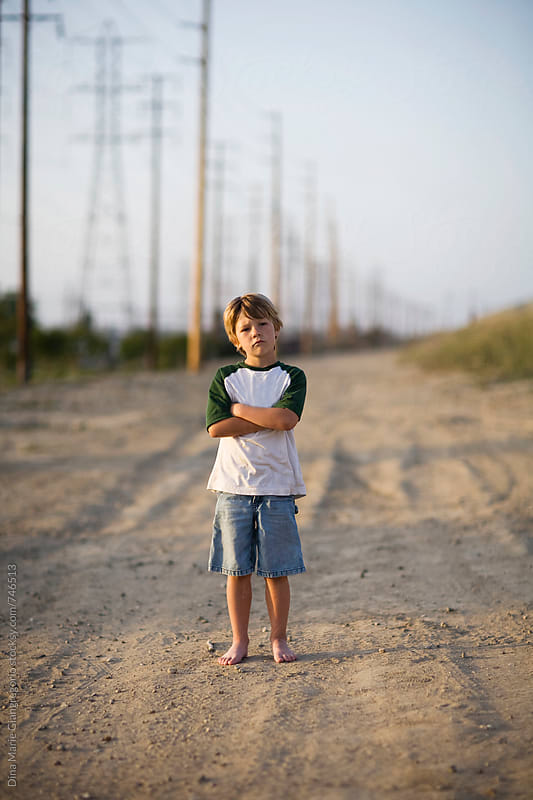 Barefoot Boy Standing on Dirt Road by Dina Giangregorio for Stocksy United