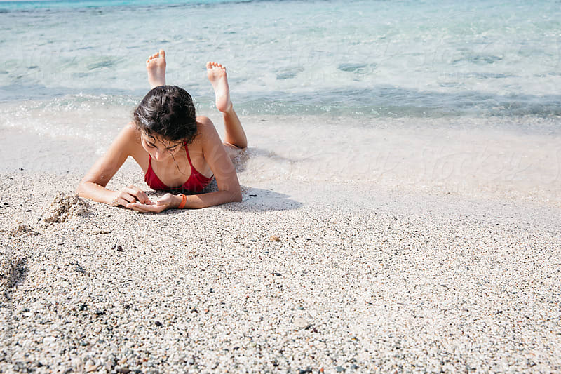 Girl on a white sandy beach by herself by Beatrix Boros for Stocksy United