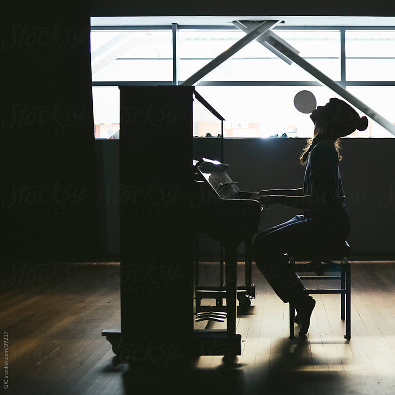 Silhouette of a woman playing piano by Simone Becchetti for Stocksy United