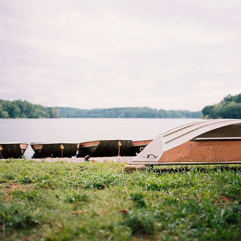 Overturned boats on the shore of a reservoir by Joey Pasco for Stocksy United