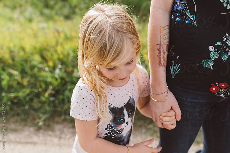Young girl holding mothers hand by Carey Shaw for Stocksy United