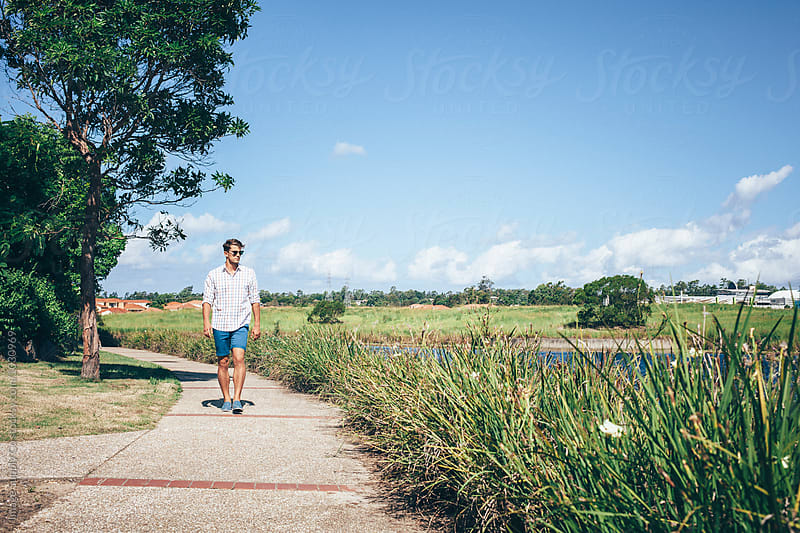 Young man taking scenic walk along river by Image Supply Co for Stocksy United