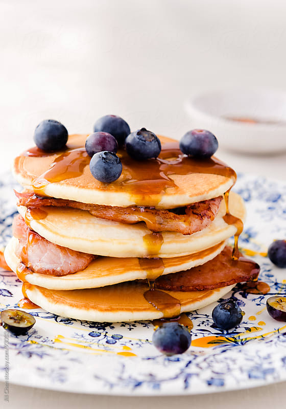 Stack of pancakes layered with bacon, blueberries and maple syru by Jill Chen for Stocksy United