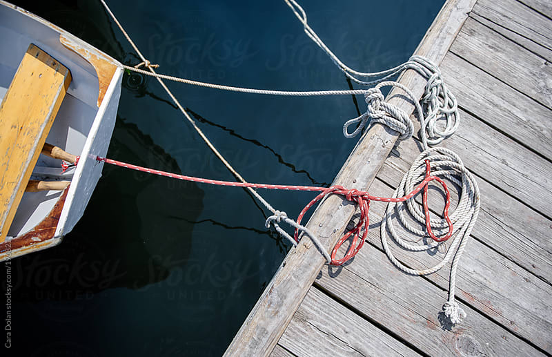 Dock, ropes and rowboat by Cara Dolan for Stocksy United