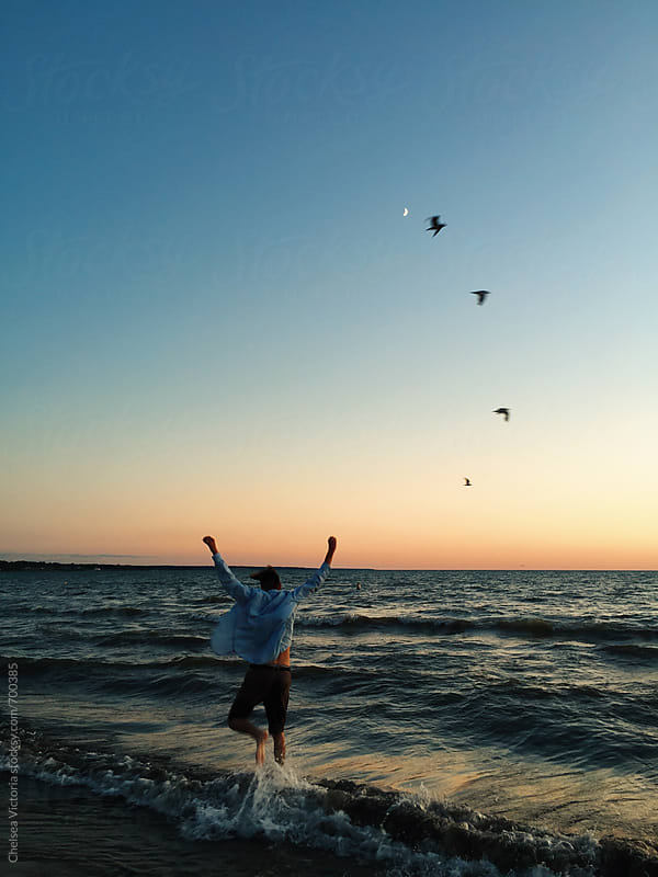 A young man having fun at the beach at sunset by Chelsea Victoria for Stocksy United
