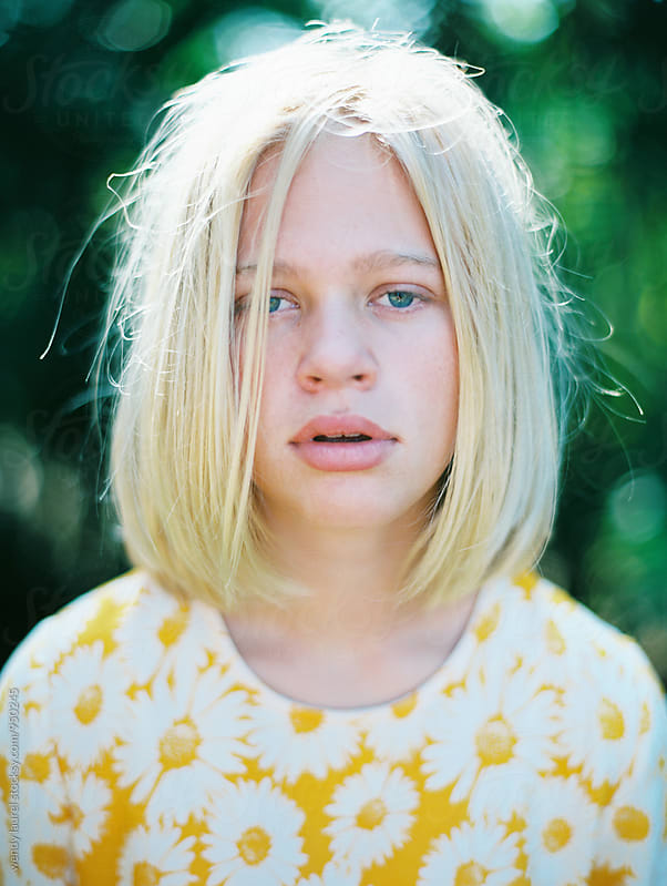 portrait of girl with blonde hair in bob and yellow floral dress by wendy laurel for Stocksy United