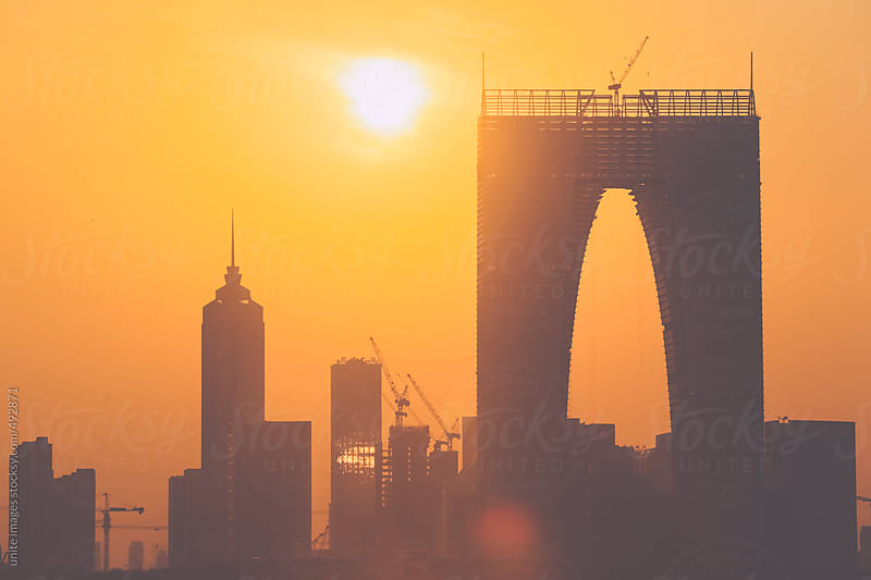 silhouette of modern skyscrapers during sunset by unite images for Stocksy United