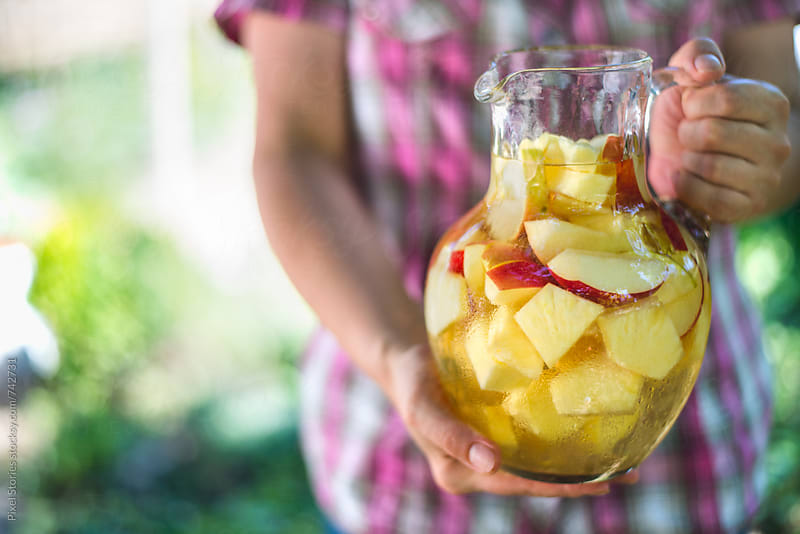 Woman holding jug of homemade white sangria by Pixel Stories for Stocksy United