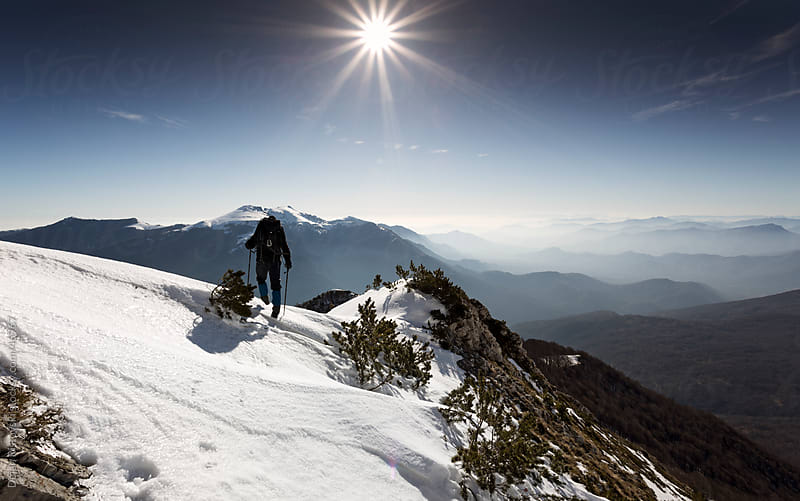 Male climber climbing a snowy ridge by Dejan Ristovski for Stocksy United