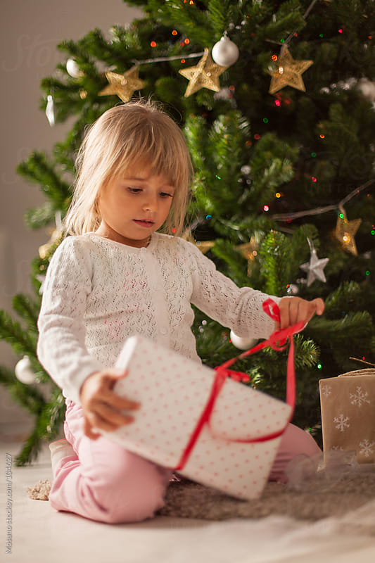 Cute Girl Opening Christmas Gift  by Mosuno for Stocksy United