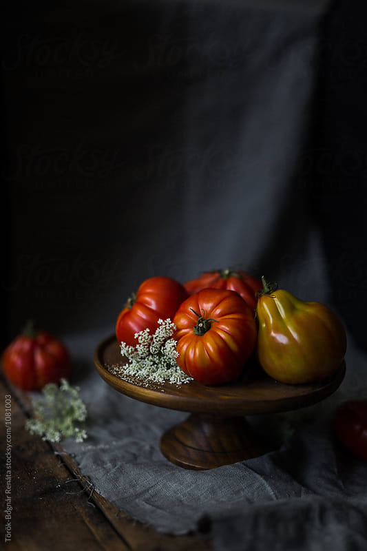 Fresh tomatoes on a rustic wooden plate  by Török-Bognár Renáta for Stocksy United
