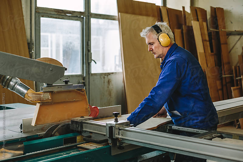 male woodworker with yellow protection earmuffs working on a benchsaw