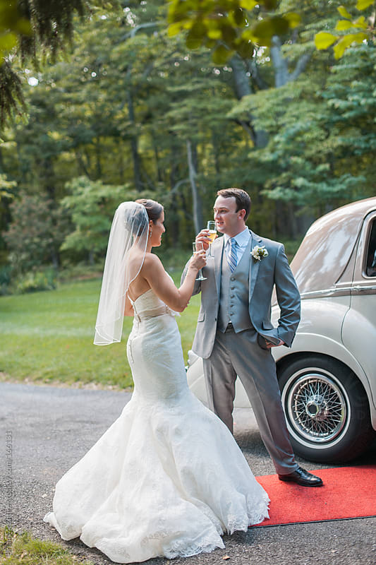 Bride and Groom Toast Champagne Near Classic Luxury Car by Brian McEntire for Stocksy United