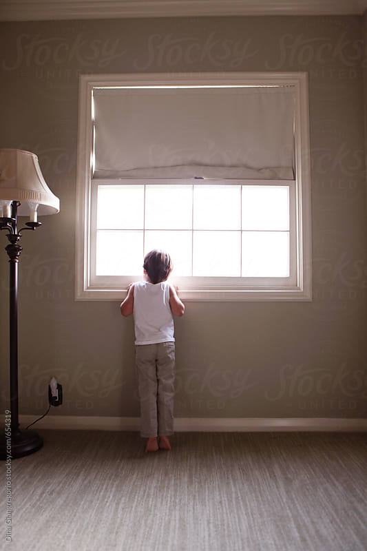 Back View Of Little Boy Looking Out Square Window by Dina Giangregorio for Stocksy United