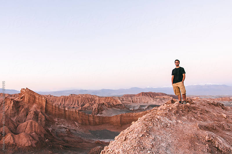 Young man on rocky desert landscape in Valley of the Moon, Chile by Alejandro Moreno de Carlos for Stocksy United