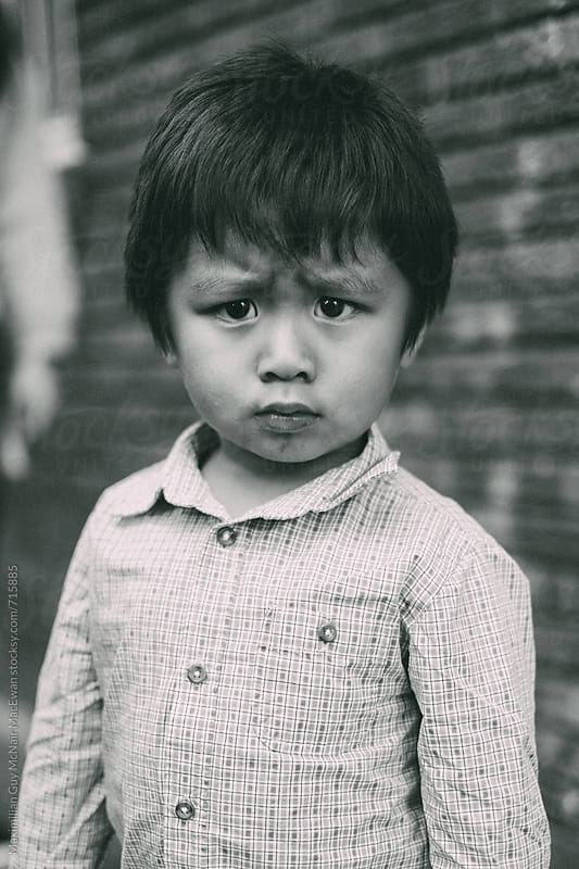 A cute kid with a big frown by Maximilian Guy McNair MacEwan for Stocksy United