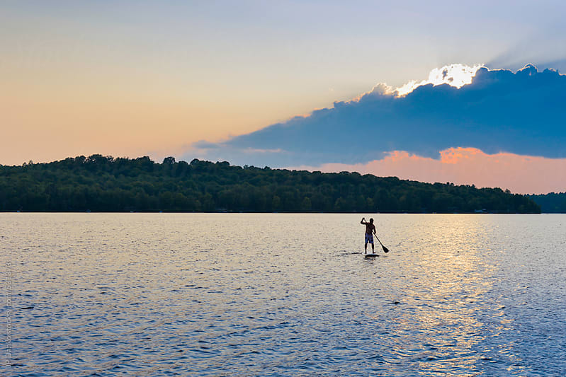 Man With Stand Up Paddleboard on Quiet Cottage Lake At Sunset by JP Danko for Stocksy United