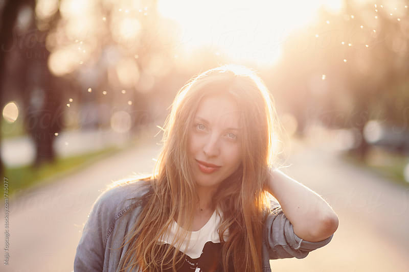 Young beautiful woman in the park at sunset by Maja Topcagic for Stocksy United