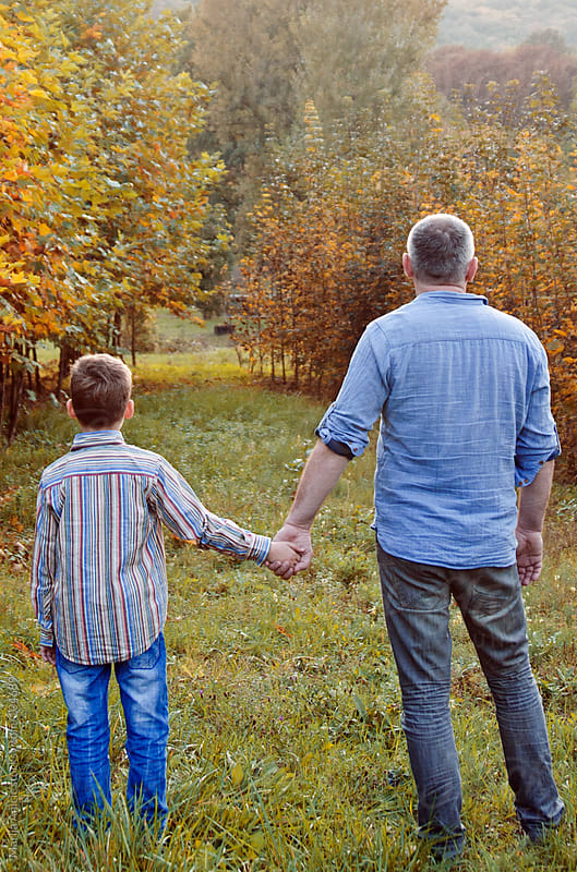 father and son holding hands and looking to the autumn trees  by Marija Anicic for Stocksy United