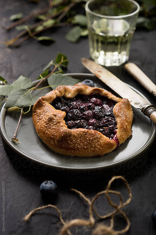 Homemade blueberry galette on a plate. by Darren Muir for Stocksy United
