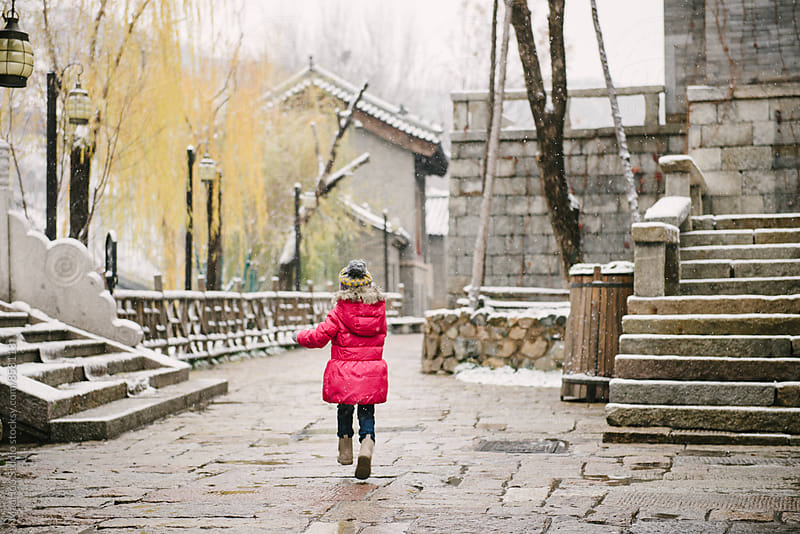 Baby girl running in a snow old town by MaaHoo Studio for Stocksy United