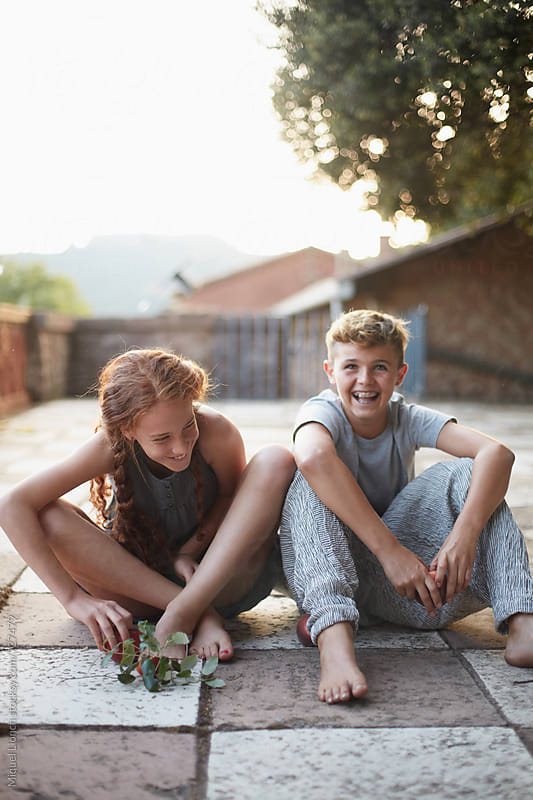 Couple of adolescents in a happy moment by Miquel Llonch for Stocksy United