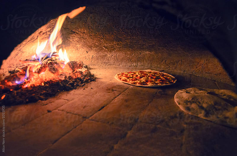 Veggie pizzas in firewood oven in the darkness by Alice Nerr for Stocksy United