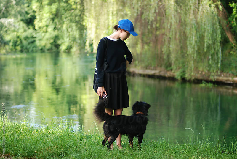 A young woman walking with a black dog by Anna Malgina for Stocksy United