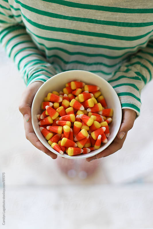 Girl in a striped shirt holding a bowl of candy corn by Carolyn Lagattuta for Stocksy United