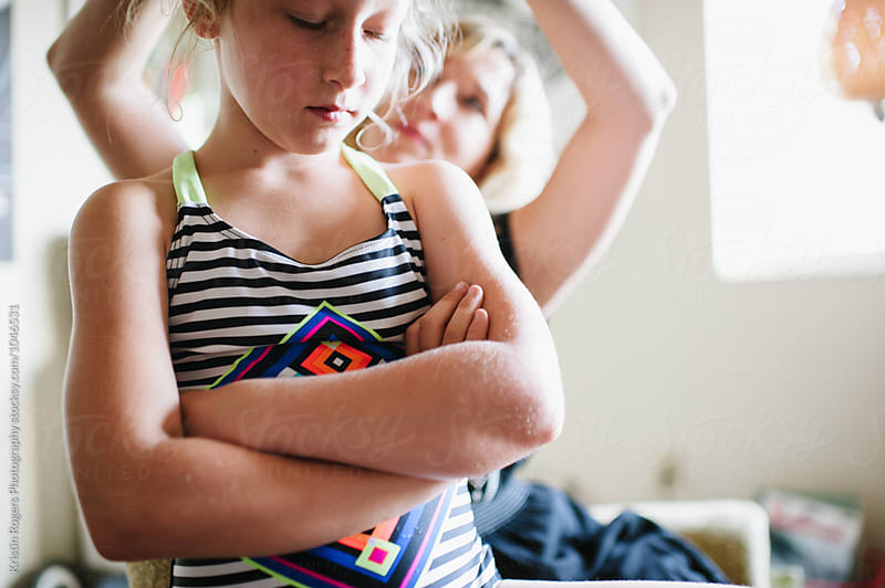 Mom putting daughters hair in bun by Kristin Rogers Photography for Stocksy United