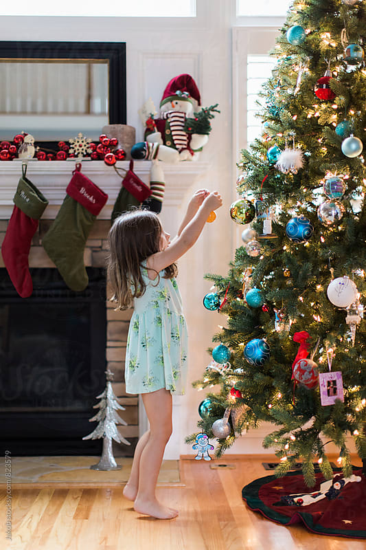 Cute young girl in nightgown hanging christmas ornaments by Jakob for Stocksy United