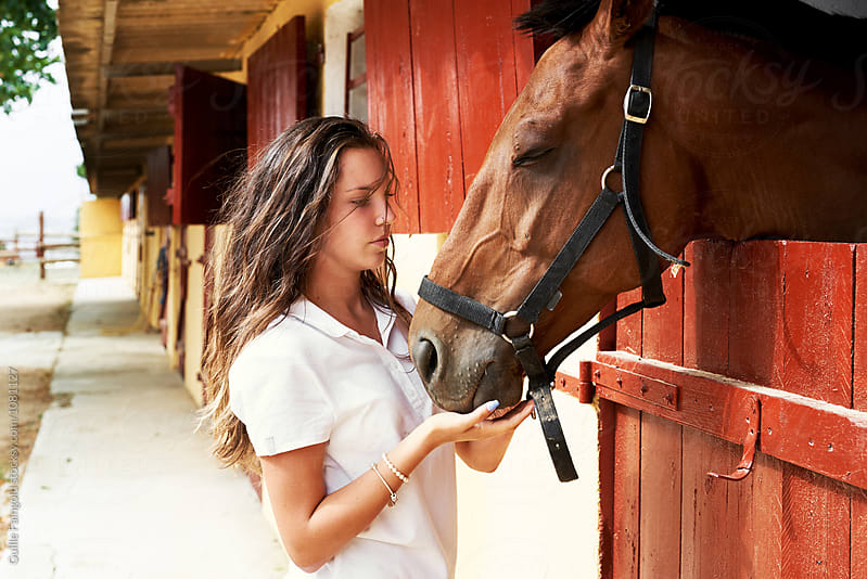 Brunette teen holding horse's mouth by Guille Faingold for Stocksy United