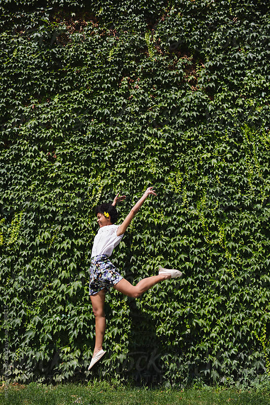 Girl jumping in front of a wall covered with ivy by michela ravasio for Stocksy United