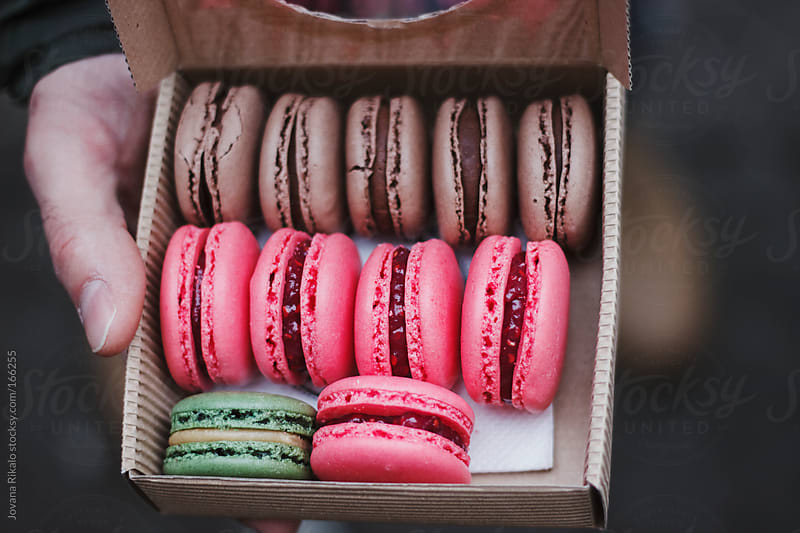 Man holding macarons in a takeaway box by Jovana Rikalo for Stocksy United