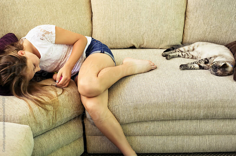 Girl on her electronic device and cat laying on the couch by Carolyn Lagattuta for Stocksy United