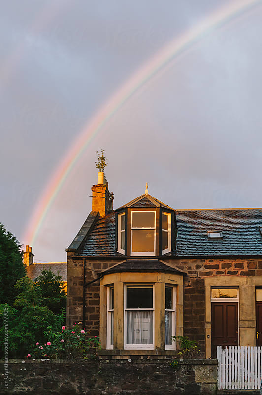 Rainbow over Scottish house by Jen Grantham for Stocksy United