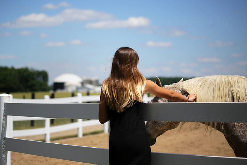 A Teen Girl Petting A White Horse by ALICIA BOCK for Stocksy United