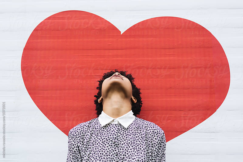 Girl looks up with a red heart drawn in the background by michela ravasio for Stocksy United