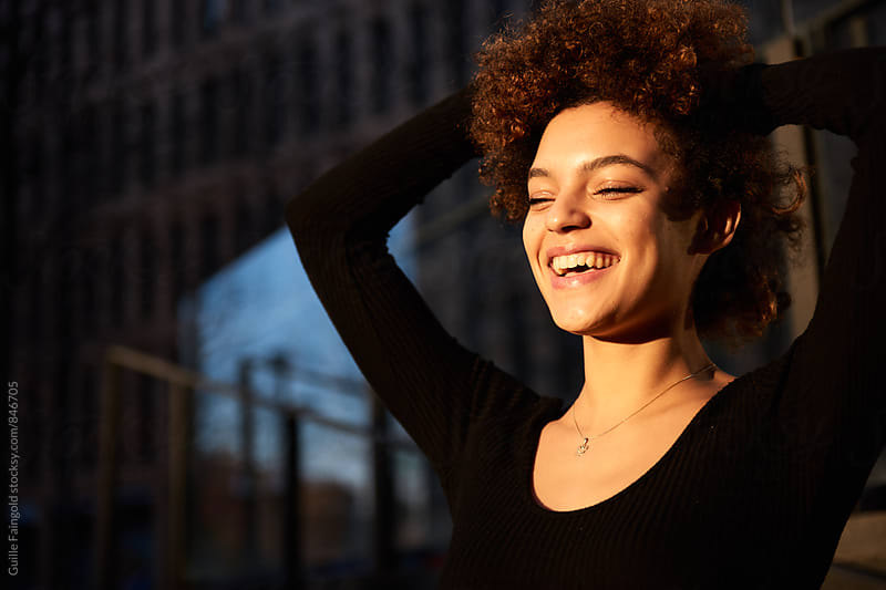 Attractive smiling woman with afro by Guille Faingold for Stocksy United