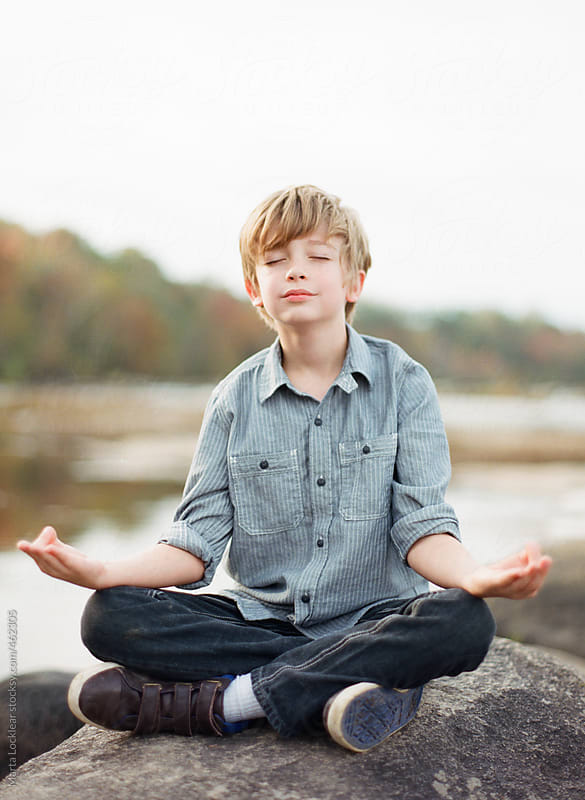 Young boy meditating on a river rock by Marta Locklear for Stocksy United