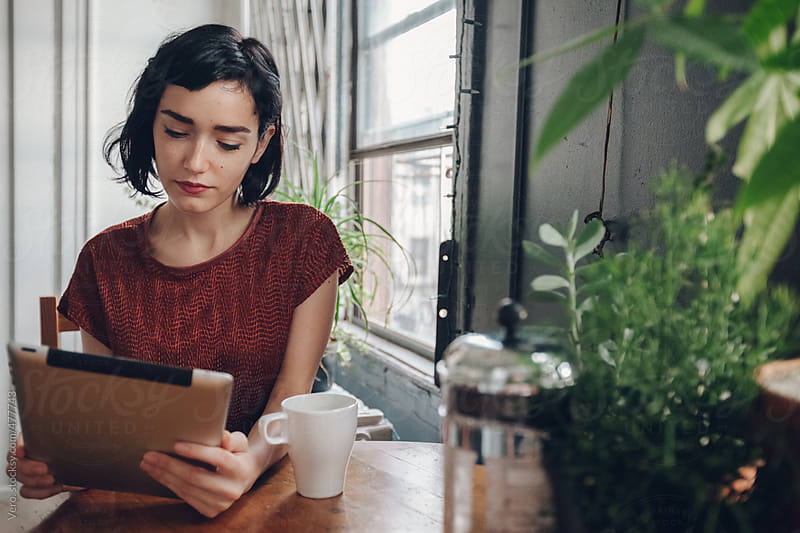Brunette using a digital tablet while drinking a coffee by Good Vibrations Images for Stocksy United